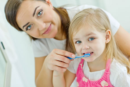 Mom and Daughter brushing their teeth - Pediatric Dentist in Littleton, CO